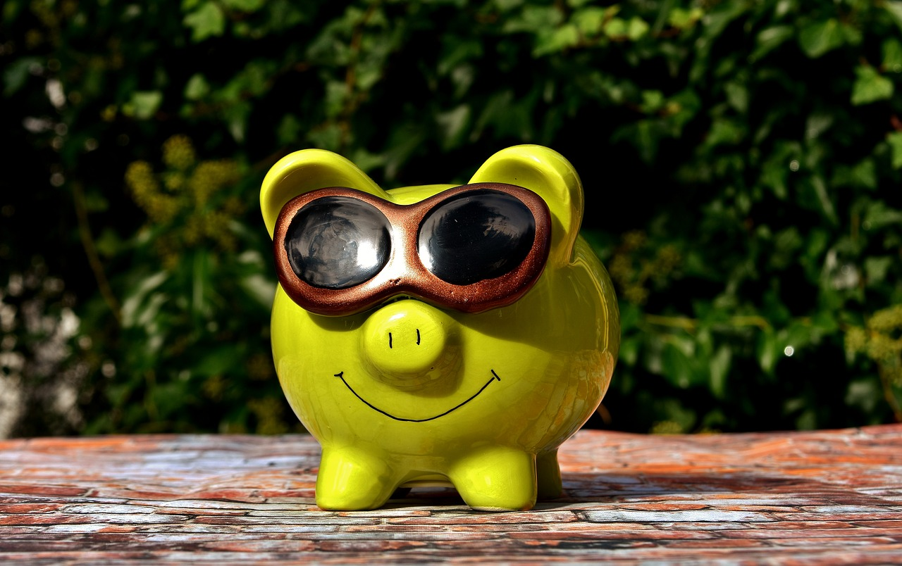 A yellow piggy bank with sunglasses on