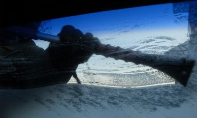 A man using a scarper and antifreeze on a frozen windscreen