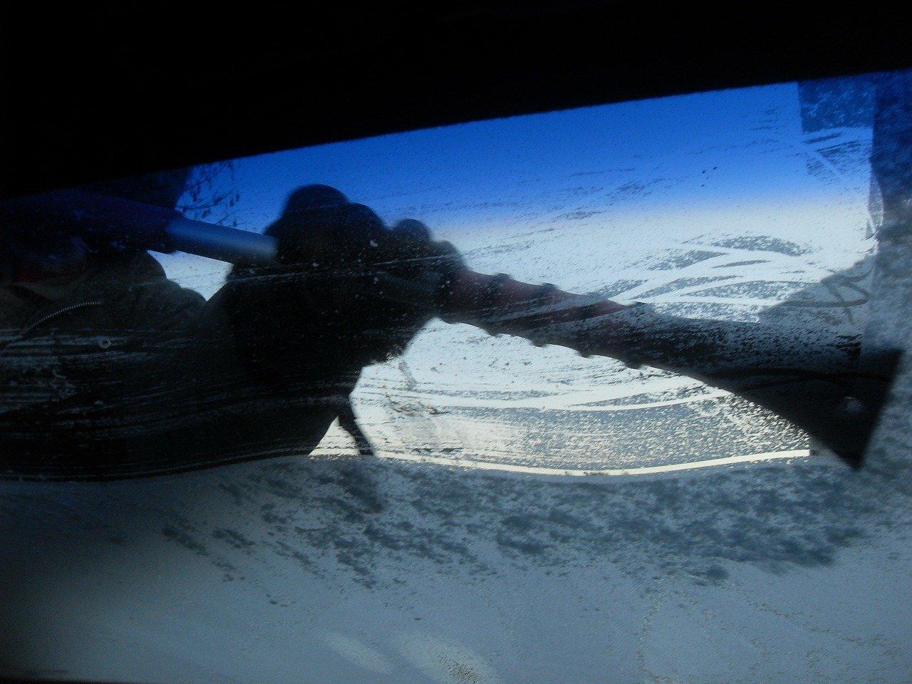 A man using a scarper and antifreeze on a frozen windscreen