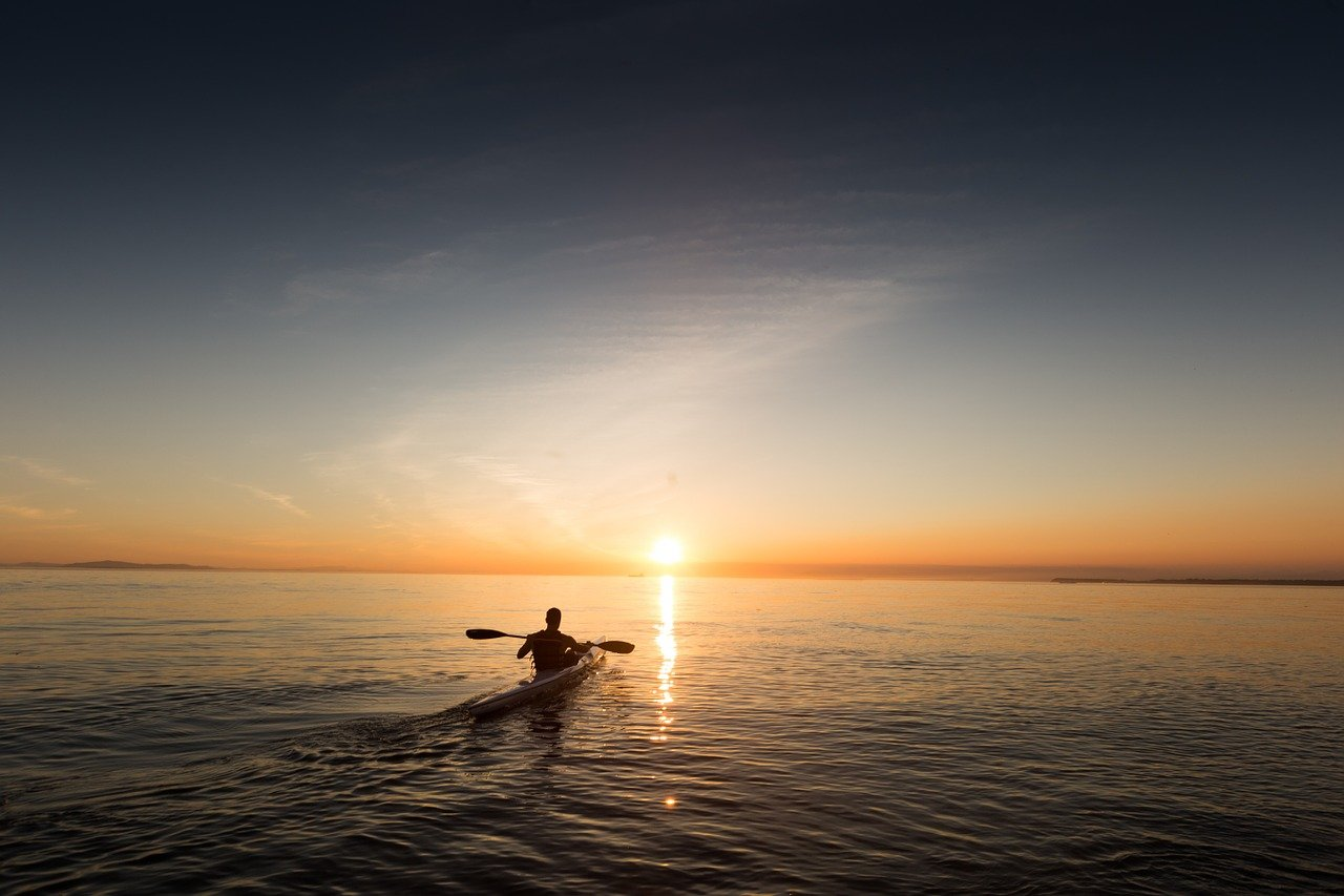 A man in a kayak at sunset