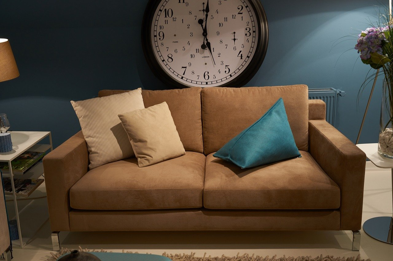 A snall couch in front of a clock